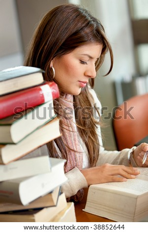 Beautiful woman portrait studying at a library