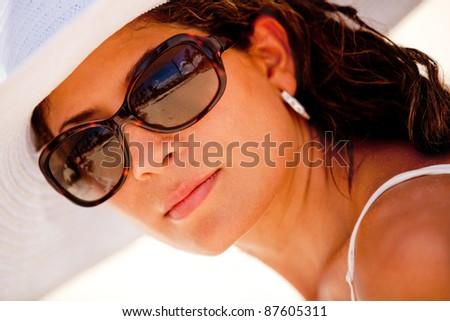 Beautiful woman portrait wearing sunglasses and a hat - stock photo