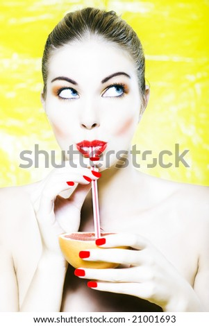 beautiful woman portrait with colorful make-up  and background drinking grapefruit juice with straw - stock photo