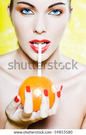 beautiful woman portrait with colorful make-up  and background drinking orange juce with straw - stock photo