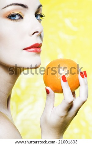 beautiful woman portrait with colorful make-up  and background holding a mandarin - stock photo