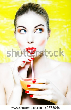 beautiful woman portrait with colorful makeup  and background drinking grapefruit juice with straw - stock photo