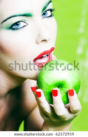 beautiful woman portrait with colorful makeup  and background holding apple - stock photo