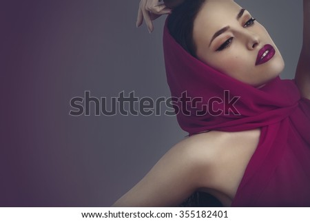 beautiful woman portrait with magenta scarf and makeup