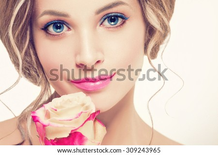 Beautiful woman portrait with perfect make up pink lips and nails blue eyes and rose flower - stock photo