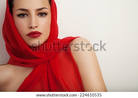 beautiful woman portrait with red lips and red veil over her head, studio shot
