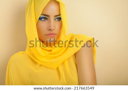 beautiful woman portrait with yellow scarf over her head, studio - stock photo