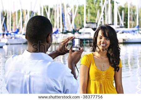 Beautiful woman posing for vacation photo at harbor with sailboats - stock photo