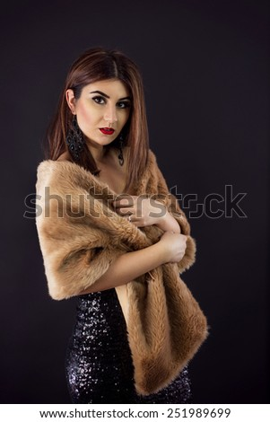 Beautiful woman posing in a sexy black dress and fur stole. - stock photo