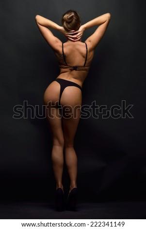beautiful woman posing in black lingerie in studio. Back view. - stock photo