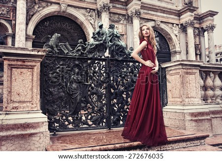 Beautiful woman posing long red dress in San Marco Square, Venice, near St Mark Basilica. - stock photo