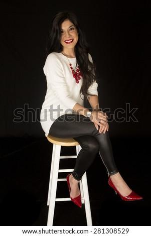 Beautiful woman posing on bar stool smiling - stock photo