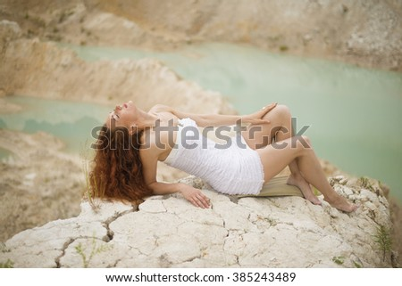 Beautiful woman posing on beach Summer relax portrait, beautiful woman with red hair look at camera Curly redhead woman with hand on hair against outdoor background Space for inscription. Closed eyes - stock photo