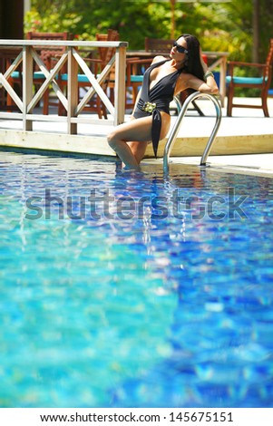 Beautiful woman posing on stairs of swimming pool