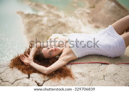 Beautiful woman posing on the sunset beach Summer relax portrait, beautiful woman with red hair look at camera Curly redhead woman with hand on hair against outdoor background Space for inscription - stock photo