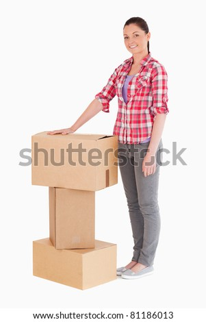 Beautiful woman posing with cardboard boxes while standing against a white background
