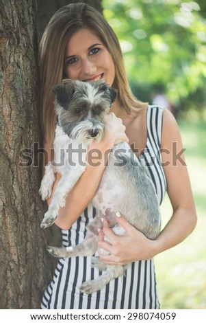 Beautiful woman posing with dog outdoor - stock photo