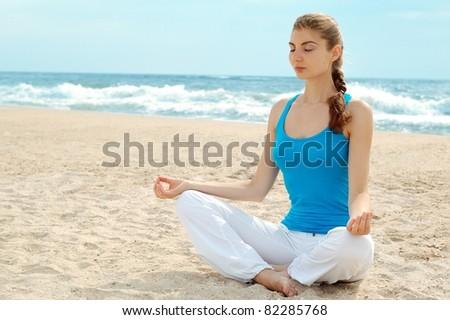 Beautiful woman practice yoga on the beach - stock photo