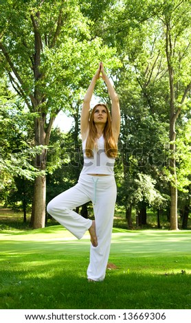 Beautiful woman practice yoga outdoors in nature environment.