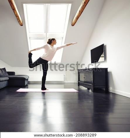 Beautiful woman practicing yoga exercises in living room. Fit female standing on one leg exercising at home. - stock photo