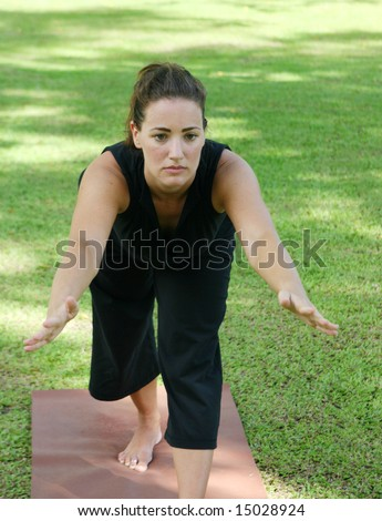 Beautiful woman practicing yoga in the park. - stock photo