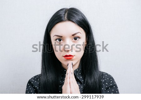 Beautiful woman praying to God. On a gray background.