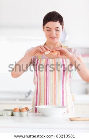 Beautiful woman preparing a cake in a kitchen - stock photo
