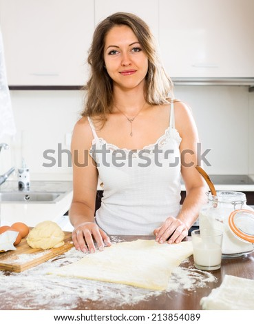 beautiful woman preparing cakes of dough at kitchen - stock photo