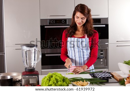 Beautiful woman preparing dinner for tonight by cutting the vegetables - stock photo