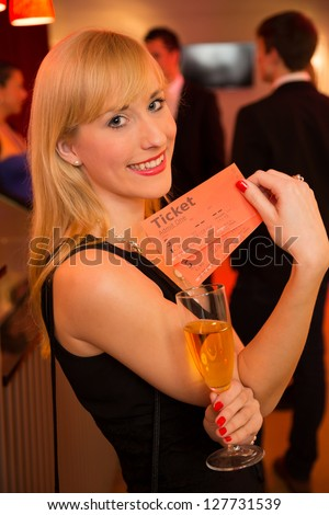 Beautiful woman presenting tickets or admission passes for a theater, concert or cinema - stock photo