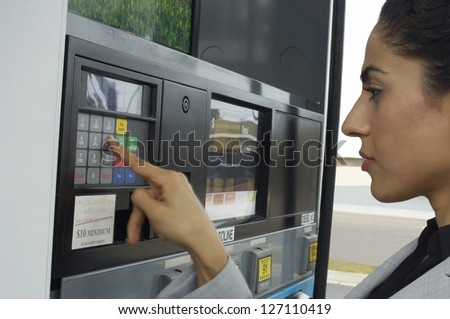 Beautiful woman pressing button of ATM machine at petrol pump