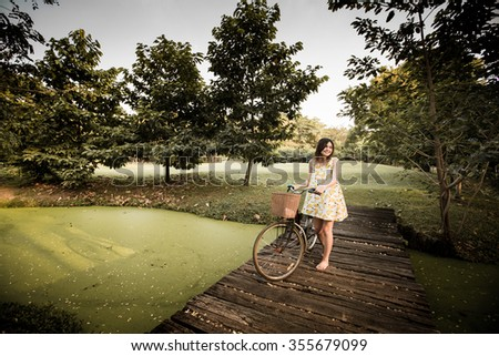 Beautiful woman pushes old bike in a wheat field. - stock photo
