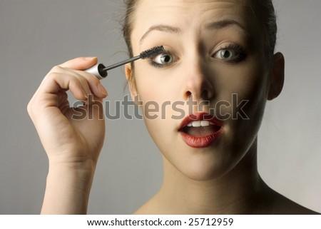 Beautiful woman putting mascara on her eyelash, daily morning routine - stock photo
