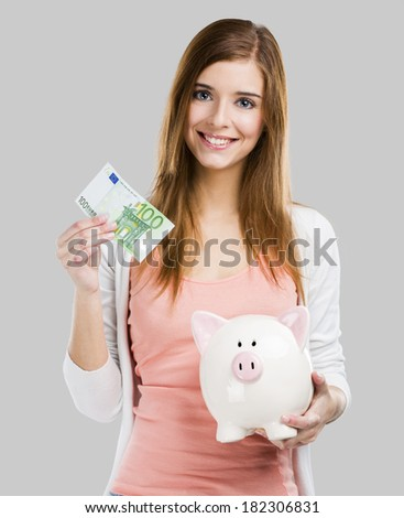 Beautiful woman putting money in a piggy bank, isolated over white background