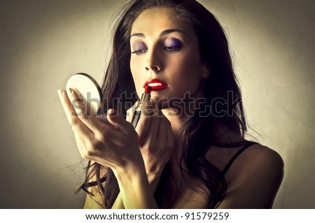 Beautiful woman putting on some makeup - stock photo