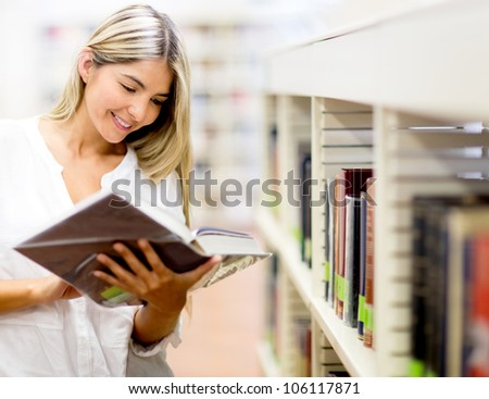 Beautiful woman reading a book at the library