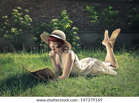 beautiful woman reading a book in the garden - stock photo
