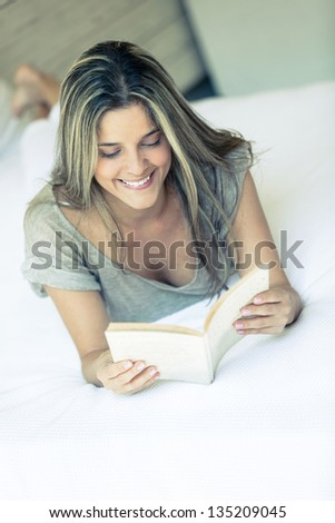 Beautiful woman reading a book looking happy - stock photo