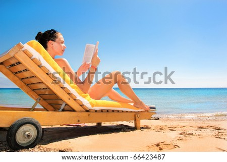 beautiful woman reading a book on beach - stock photo