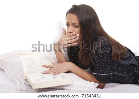 beautiful woman reading a book on the bed and feeling sleepy - stock photo