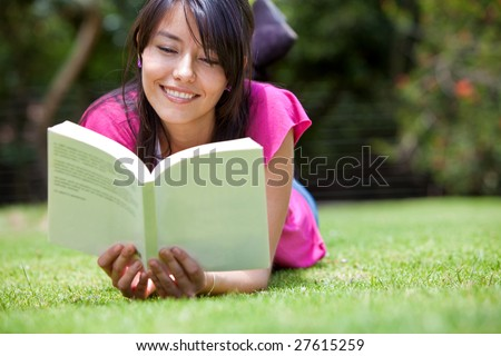 Beautiful woman reading a book outdoors