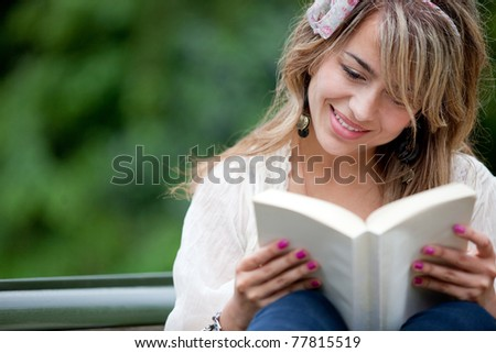 Beautiful woman reading a book outdoors and smiling