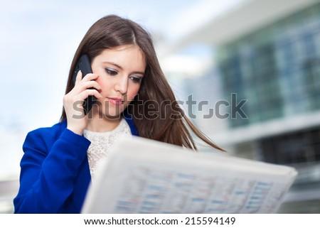 Beautiful woman reading a newspaper - stock photo