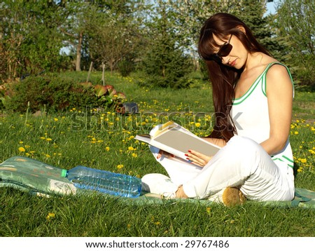 Beautiful woman reading happy a book in garden, green nature outdoor
