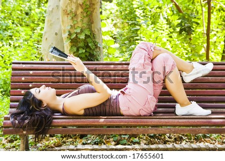Beautiful woman reading in a park bench. - stock photo