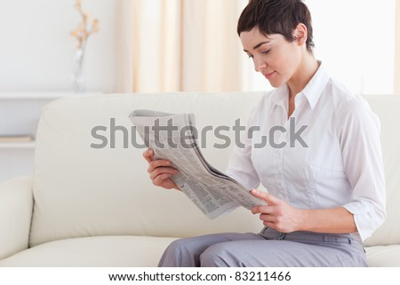 Beautiful woman reading the news in the living room