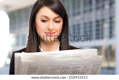 Beautiful woman reading the newspaper outdoor - stock photo