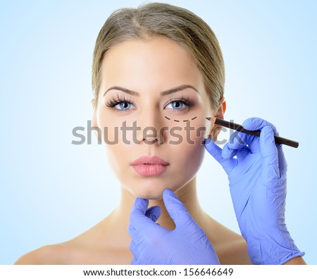 Beautiful woman ready for cosmetic surgery, female face with doctor's hands drawing lines on skin, over blue - stock photo