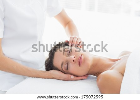 Beautiful woman receiving head massage in health spa - stock photo