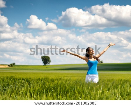 Beautiful woman rejoicing her freedom in nature standing in a field of young green wheat with outstretched arms and a lovely smile on her face looking up at the sun